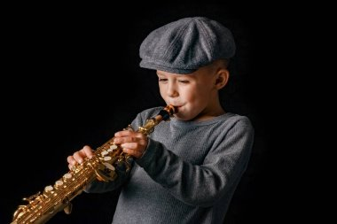 happy child plays saxophone in studio