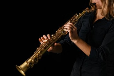 soprano saxophone in hands on a black background