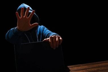 Dizüstü bilgisayarı olan bir bilgisayar korsanı masada oturuyor ve ikili kodları soyutluyor. İş hayatı tehdit sanal programları.