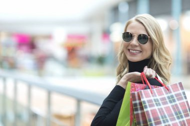 Beautiful stylish young woman in sunglasses with shopping bags,