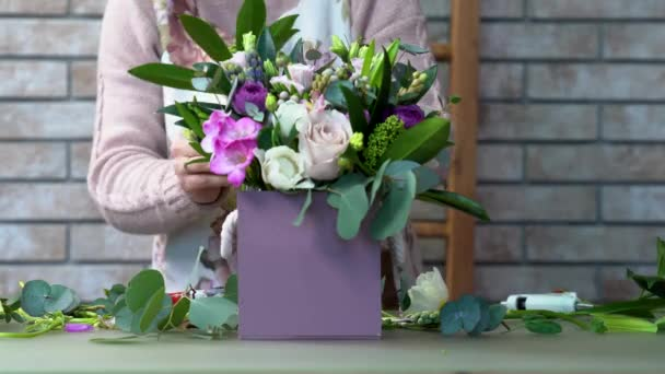 Face view of a florist in a apron making a violet shades flowers composition with roses, eustomas, hyacinths, peony, brunia, ranunculus, skimmia and eucalyptus leaves.