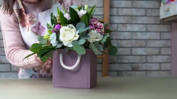 Květinářství udělal poslední krok a dokončil natáčení složení květy fialové odstíny (růže, eustomas, hyacinty, pivoňka, brunia, ranunculus, Skimmie).