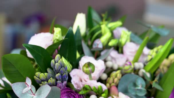 Very close view of white, rose and violet colored flowers. Tilt down camera movement. Among them roses, eustomas, hyacinths, peony, brunia, ranunculus, skimmia and eucalyptus leaves.