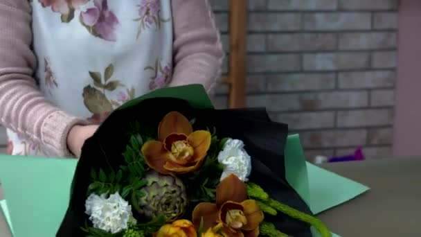 Close up of florist wraps a bouquet in green wrapping paper. Artichoke, orange orchid, white carnation, skimmia.