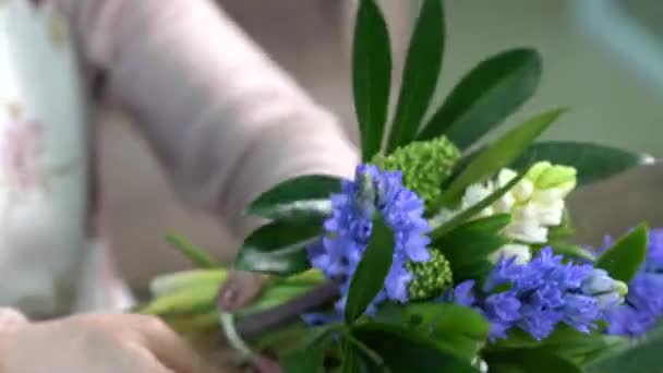 Close up of florist quickly ties a white and blue hyacinths flowers bouquet with a white twine. Composition decorated by skimmia.