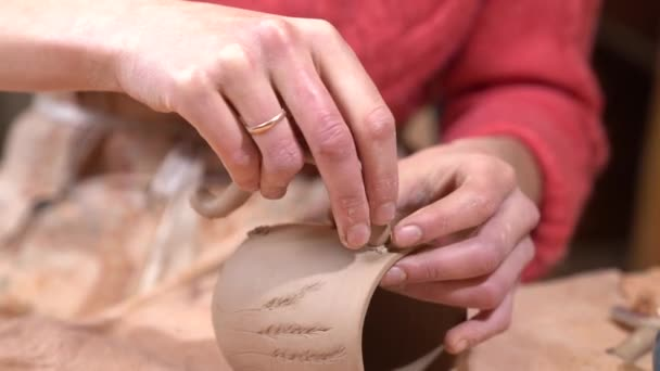 Closeup of woman ceramist clinging the handle to the raw clay cup.