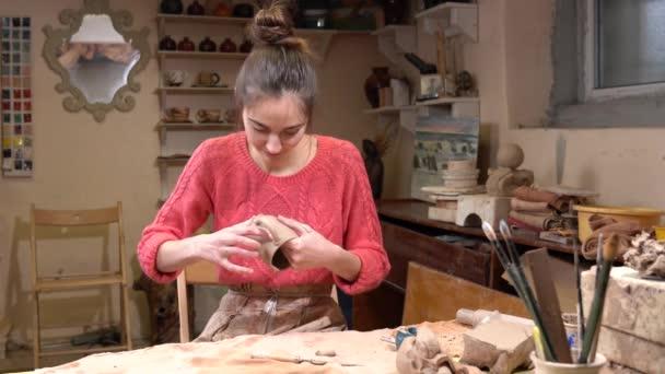Gesamtansicht der Keramikerin Mädchen Feinabstimmung den Rohton-Cup in der Keramikwerkstatt