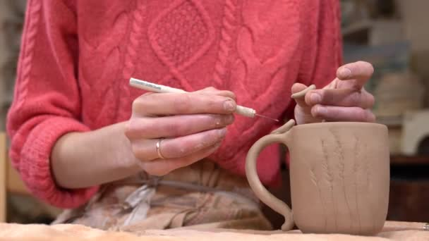Closeup of woman ceramist clinging small clay part to the raw clay cup.