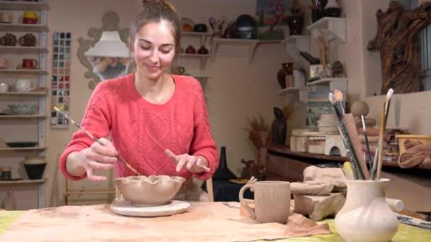 allgemeine Ansicht einer Keramikerin, die mit der Quaste in der Töpferei die Tontopfoberfläche glättet.