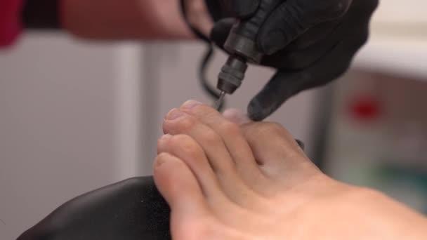 Closeup žena nohy. Odebírání nehet kutikuly a nehtu, leštění s nohou pedikúra vrtací stroj