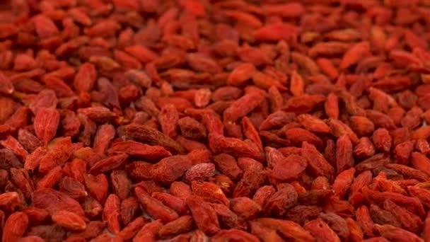 Vollbild-Hintergrund aus organischen getrockneten Goji-Beeren, die sich auf dem Drehtisch drehen. Schlupflöcher. Nahaufnahme Makro. Schräger Blick.