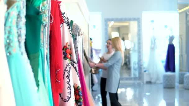 Kupující na pozadí výběru šatů v obchod s oblečením žen a rozmazané konzultant