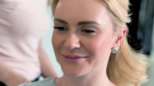 Detailní záběr šťastný šedýma očima blondýnka dělá styling v salonu krásy