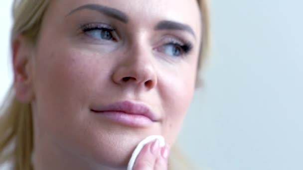 Krásná blondýnka pomocí vatové tampony. Žena, odstranění make-upu. Čištění zdravou kůži. Pojetí krásy  péče. Detailní záběr