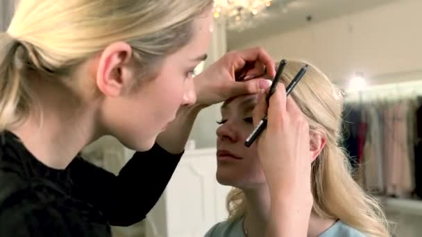 Profesionální vizážistka použití oční linky kolem očí na blond žena v salonu krásy. Krása, make-up a módní koncept