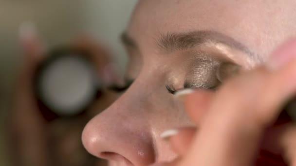 Rukou vizážista použití světlé oční make-up pomocí štětce k modelu oko. Extrémní zblízka pohled