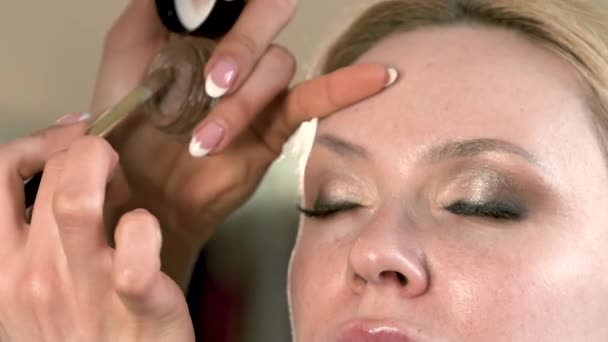 Make-up artist applying eyelash makeup to blonde models eye. Close up view.