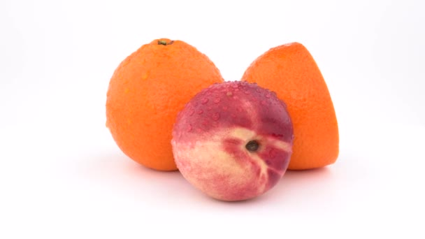 Juicy orange fruit, mandarine and nectarine with water drops rotating on white background. Isolated. Close up.