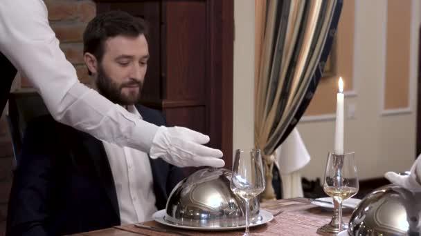 Zwei Kellner öffnen gleichzeitig die Geschirrdecke - eine Cloche, die das Gericht vor dem respektablen bärtigen Mann im Anzug zeigt. Feinschmeckerrestaurant-Konzept.