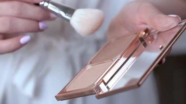 Closeup ženská ruka drží kompaktní pudr na obličej a šíří prášek na bílé stopy