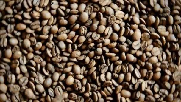 Duftende Kaffeebohnen werden in einer Pfanne geröstet. Die ganze Komposition dreht sich um die Kamera.