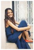 Fotografie  Porträt einer attraktiven, jungen und eleganten indischen Asiatin, die tagsüber auf Stufen in der Stadt sitzt. sie lächelt.