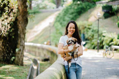 Portrait of a young Pan Asian woman with dog in a green park on a warm day in the park. The dog is a toy breed shih tzuh.