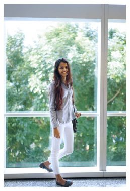 Portrait of a young Indian woman standing near the glass wall wearing formal clothing. She is casually smiling back towards the camera in a natural way.