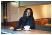 Fotografie Porträt einer jungen, attraktiven und eleganten indischen Asiatin in einem warmen und gemütlichen Café. Sie lacht auf natürliche, entspannte Weise.