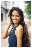 eine junge und attraktive indische Frau in einem eleganten blauen Kleid geht auf der Straße in der Stadt. sie lächelt in den Tag.