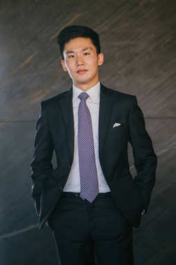 Portrait of Asian man in a professional dark suit and white shirt against  background. He has a stylish pocket square and is smiling mildly at the viewer.
