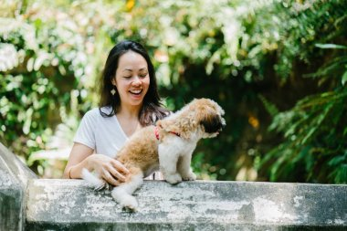 Portrait of a young, attractive pan Asian woman with her shih tzuh dog in the park. They are in the middle of a walk and they look cheerful and relaxed.