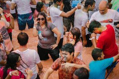 Singapore, March 3, 2018: Holi celebration in Sentosa island, Singapore. Indians and other celebrants smear colored paste and powder on one another and dance to music in a large pool in the sun.