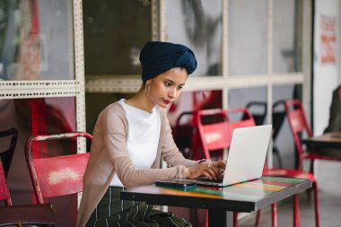 Portrait of a young, attractive Muslim woman (Asian, Arab, Malay) entrepreneur or businesswoman working on her laptop. She is dressed smartly and wears a turban (hijab, headscarf) and is sitting. stock vector