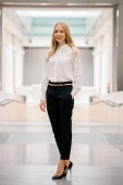 full-length, full-body shot of an attractive mature Russian woman leader. She is elegantly dressed in professional white shirt and black pants and heels and is smiling confidently.