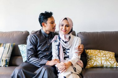 portrait of a Muslim Malay couple at home during the Muslim festival of Hari Raya in Singapore, Asia. They are sitting on their home couch