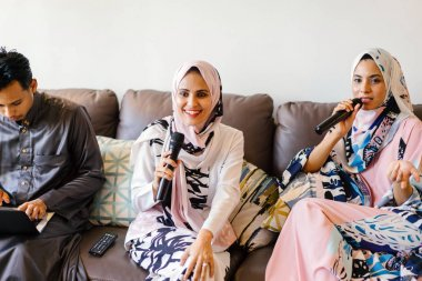 Two Muslim women in headscarves are singing karaoke on their home entertainments system over Hari Raya and enjoy each other's company.