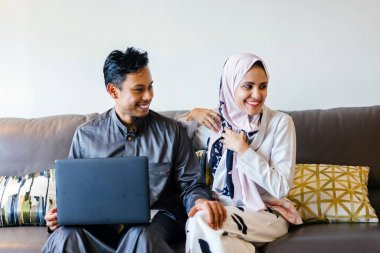 portrait of a Muslim Malay couple at home with laptop during the Muslim festival of Hari Raya in Singapore, Asia.