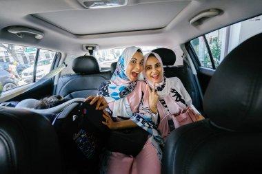Two Muslim women in headscarves in car