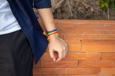 confident LGBT woman showing rainbow ribbon symbol; concept of LGBT pride, LGBTQ people, lgbt rights campaign, equality, same sex marriage, sex preference diversity in modern society