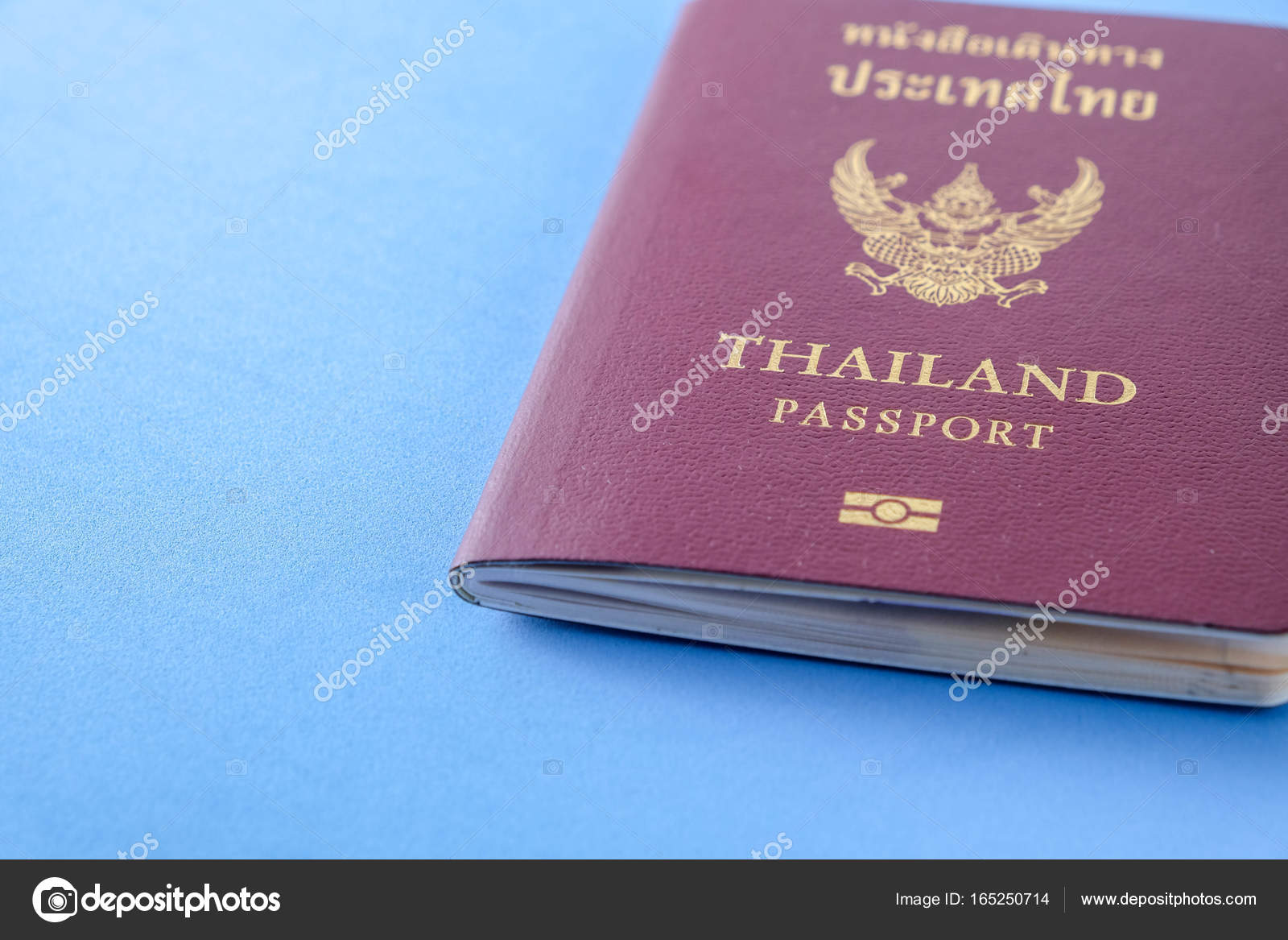 Thailand passport brown cover on blue paper background for