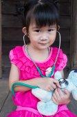 Dítě hrající lékař nebo sestra s Plyšová hračka medvěd doma