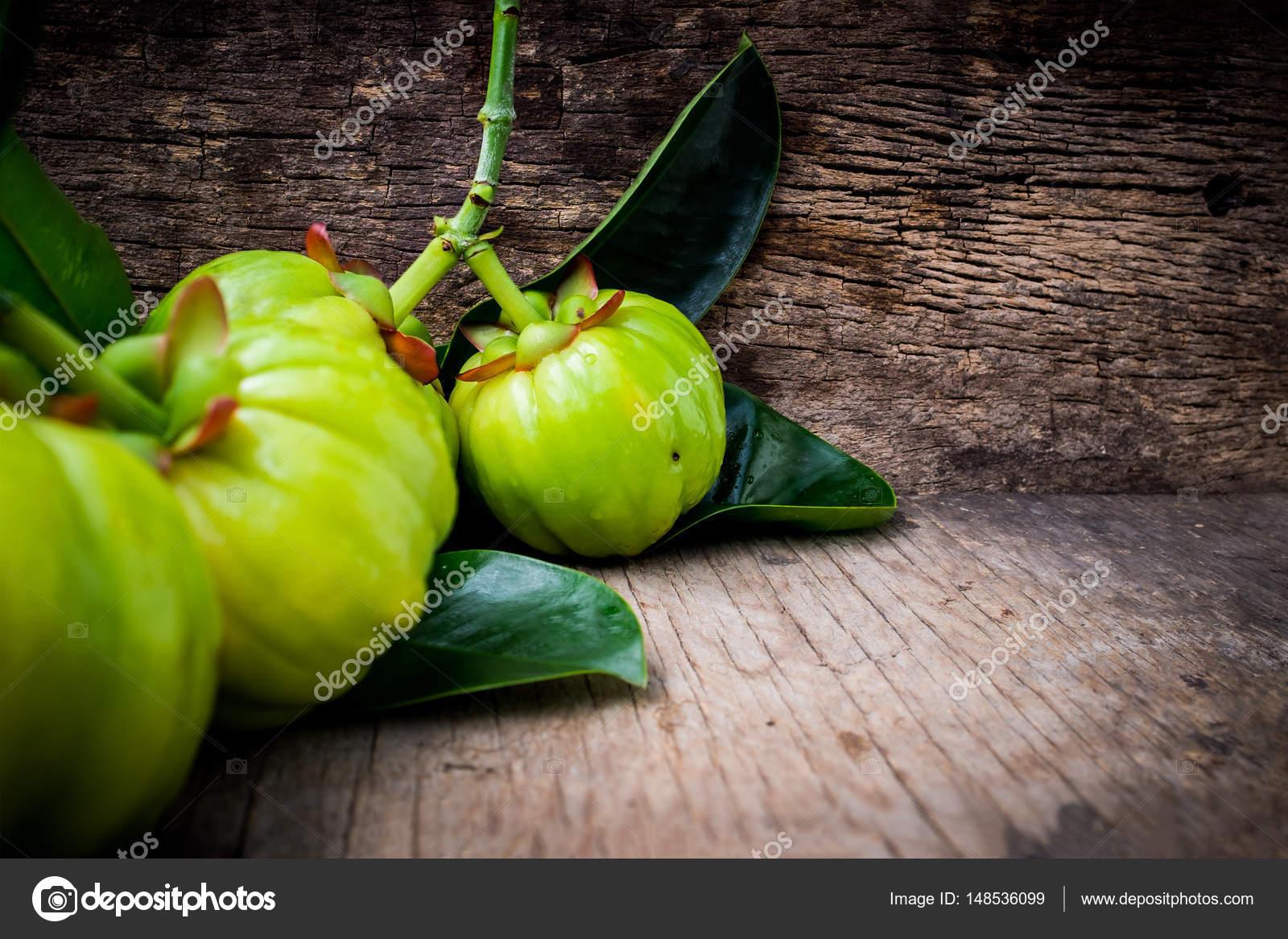 Close Up Of Garcinia Cambogia Fresh Fruit On Wood Background