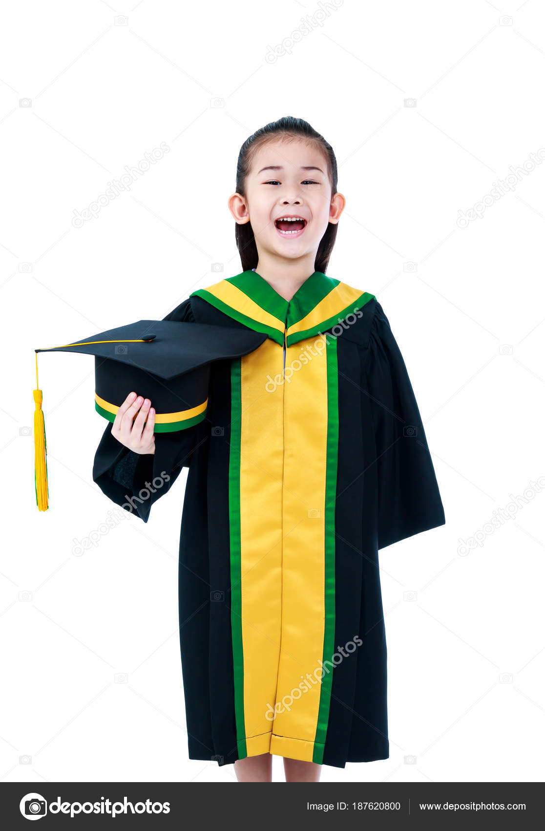 Asian Child In Graduation Gown Smiling And Holding Cap Stock
