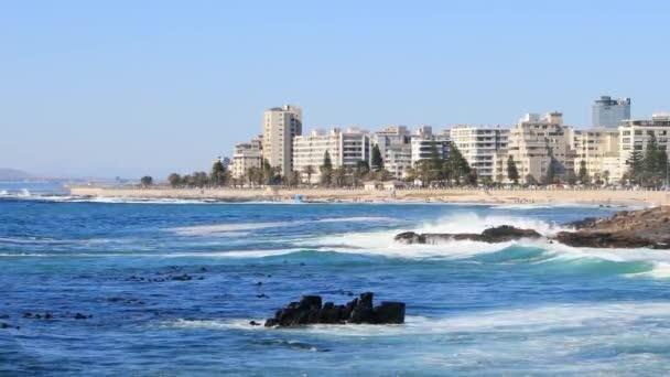 Fokváros, Dél-Afrika - 2019. október 13.: A szörfösök hullámokat fognak a Sea Point sétányán Fokváros partjainál Dél-Afrika
