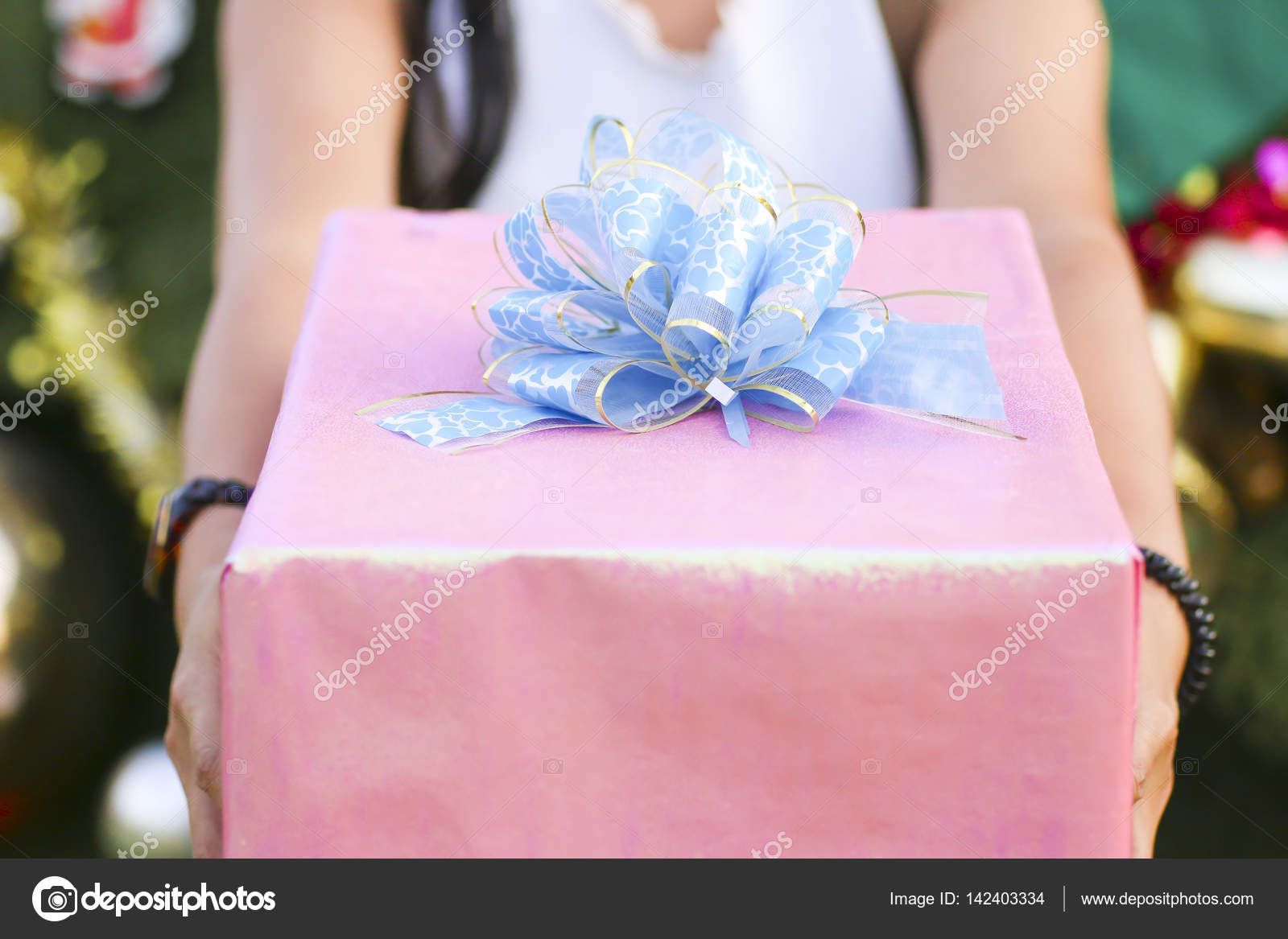 Stock Photo Close up shot of female hands holding a big gift wrapped ...