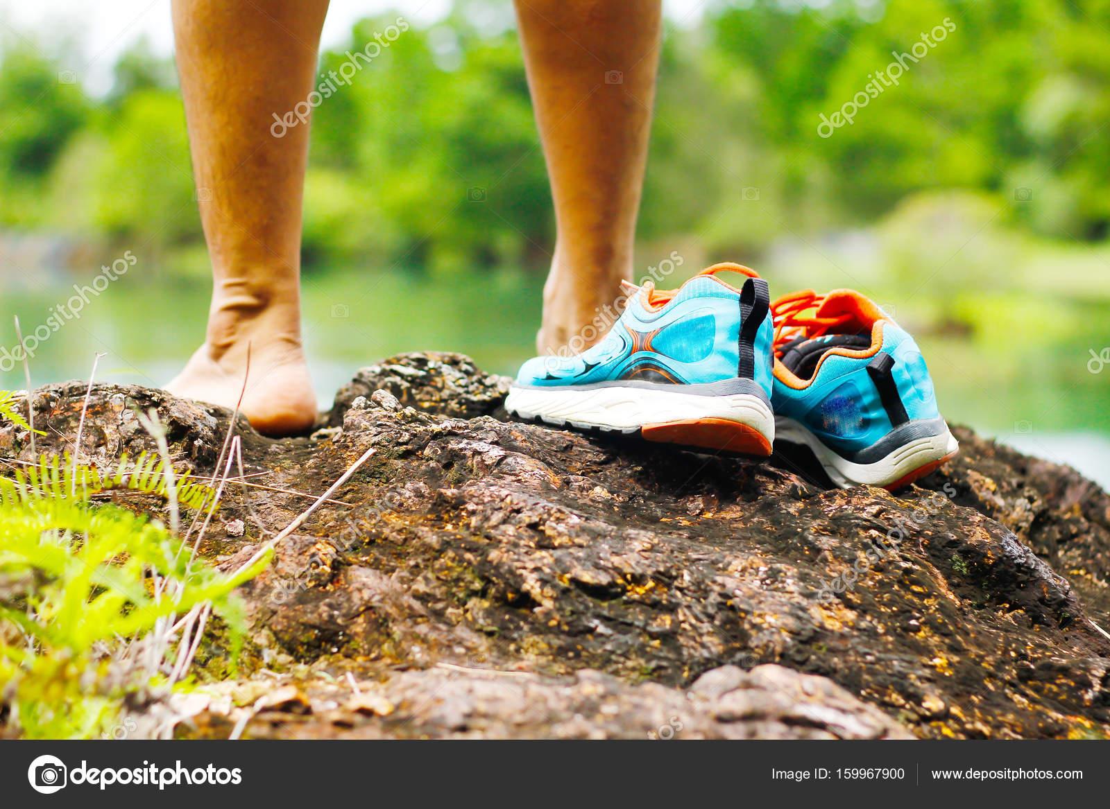 7d66c58d8e7 Στοκ φωτογραφία - παπούτσια στα βράχια δίπλα σε μια λίμνη στο βουνό —  Φωτογραφία Αρχείου