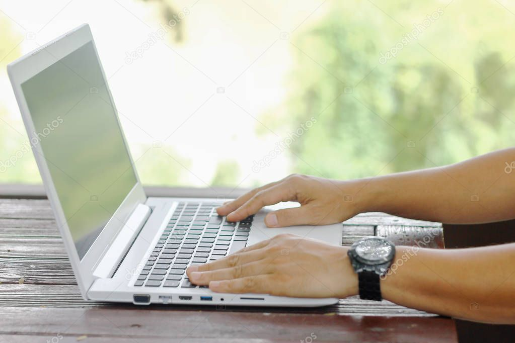 Stock photo Close up low angle view of a man working on a laptop computer sitting on wooden table with blur nature background