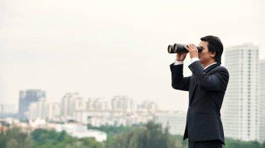 businessman with binoculars enjoying city view