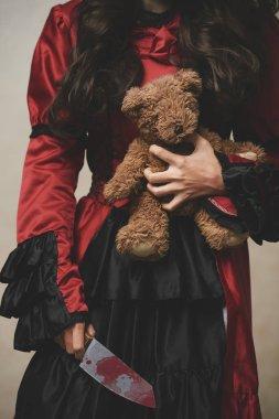 Girl holding teddy bear and knife